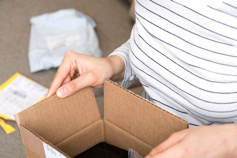 在家打包她的礼物交付命令的妇女在家